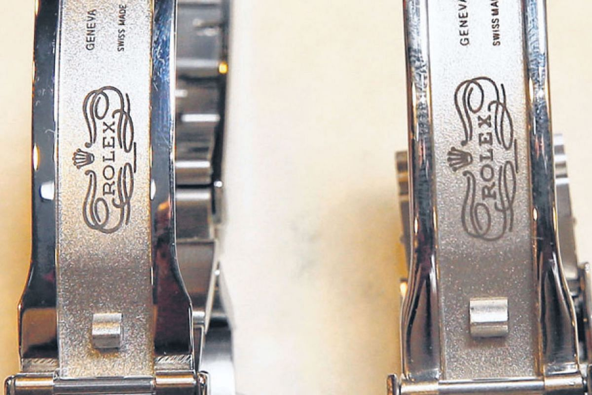 The Rolex Submariner on the left is the real McCoy. Minute differences in the logo's printing set the watches apart.