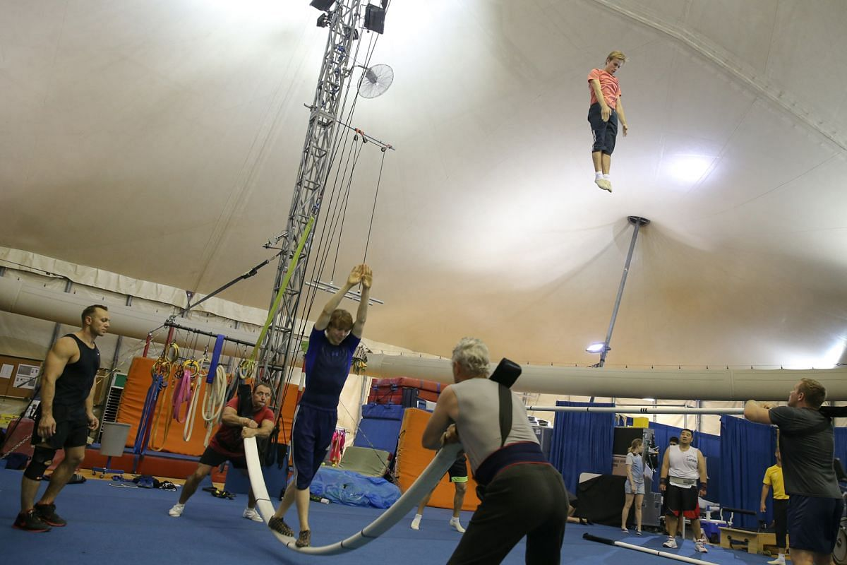Acrobats practising the Russian bars act (left), which has them leaping up to 5m high to perform flips and somersaults. An artist (left) inside a transparent cone juggles luminous balls. The wardrobe staff (far left) take care of wigs and costumes, a