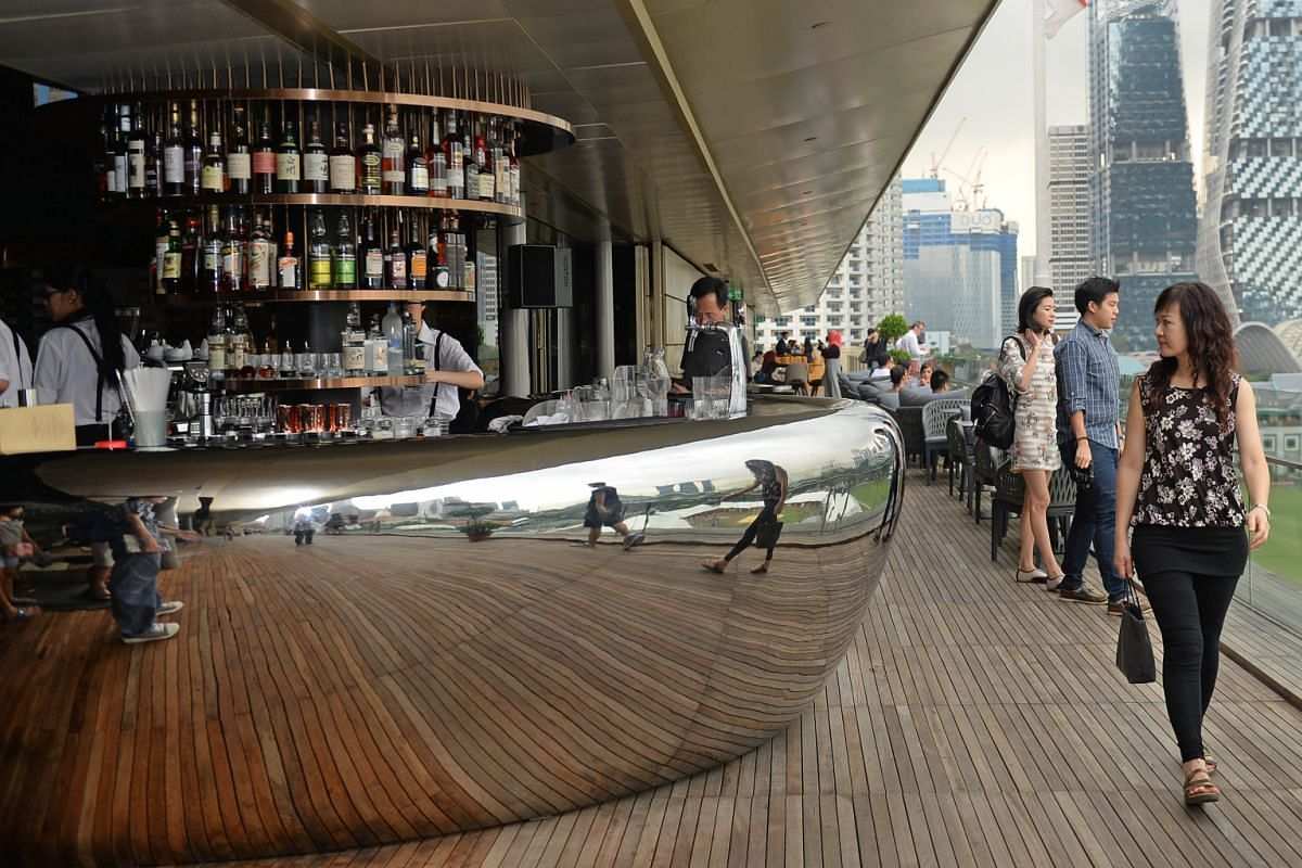 The stainless- steel bar counter (left) was crane-lifted into the deck and welded onsite. The outdoor sitting area (below) provides guests with ample photo opportunities. Smoke & Mirrors' hallway (right) has a feature wall of 600 wine glasses stacked