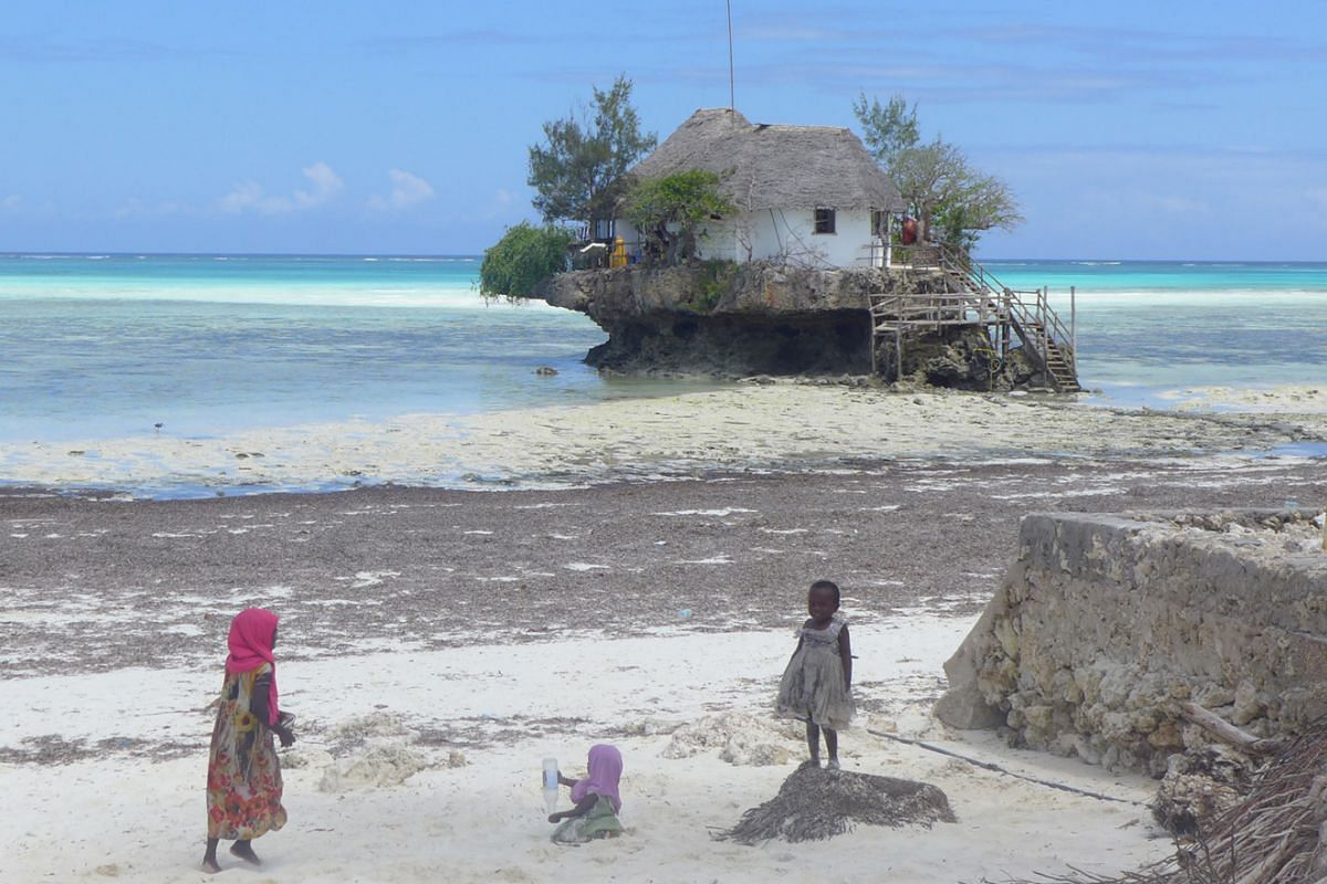 The rare Red Colubus monkey is unique to Zanzibar. Zanzibari boys splash near a traditional dhow. The Rock restaurant in Zanzibar is set in the Indian Ocean. A villa in The Residence Zanzibar. Stone Town, a Unesco World Heritage Site, is filled with
