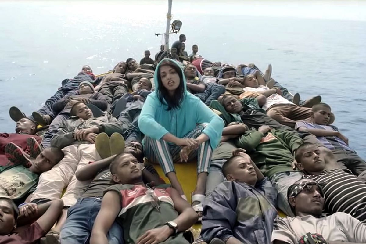 M.I.A. singing in Borders, surrounded by young men on a boat.