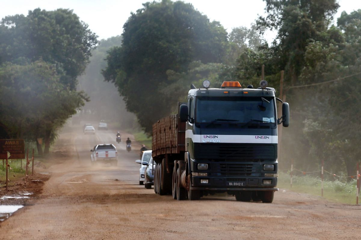 """(Above) The """"bauxite rush"""" in Pahang has led to thousands of lorries showing up in the state to transport the ore. (Left) A group of settlers from Bukit Goh taking part in a demonstration to call on the government to allow bauxite mining in their are"""