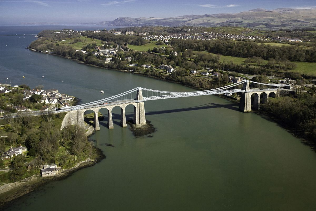 Conwy Castle (above) was named a Unesco World Heritage Site in 1986. Adventure seekers in Wales can try mountain-biking (above) through Snowdonia's forests or kayak in Llyn Padarn (top). The Menai Suspension Bridge designed by Scottish civil engineer