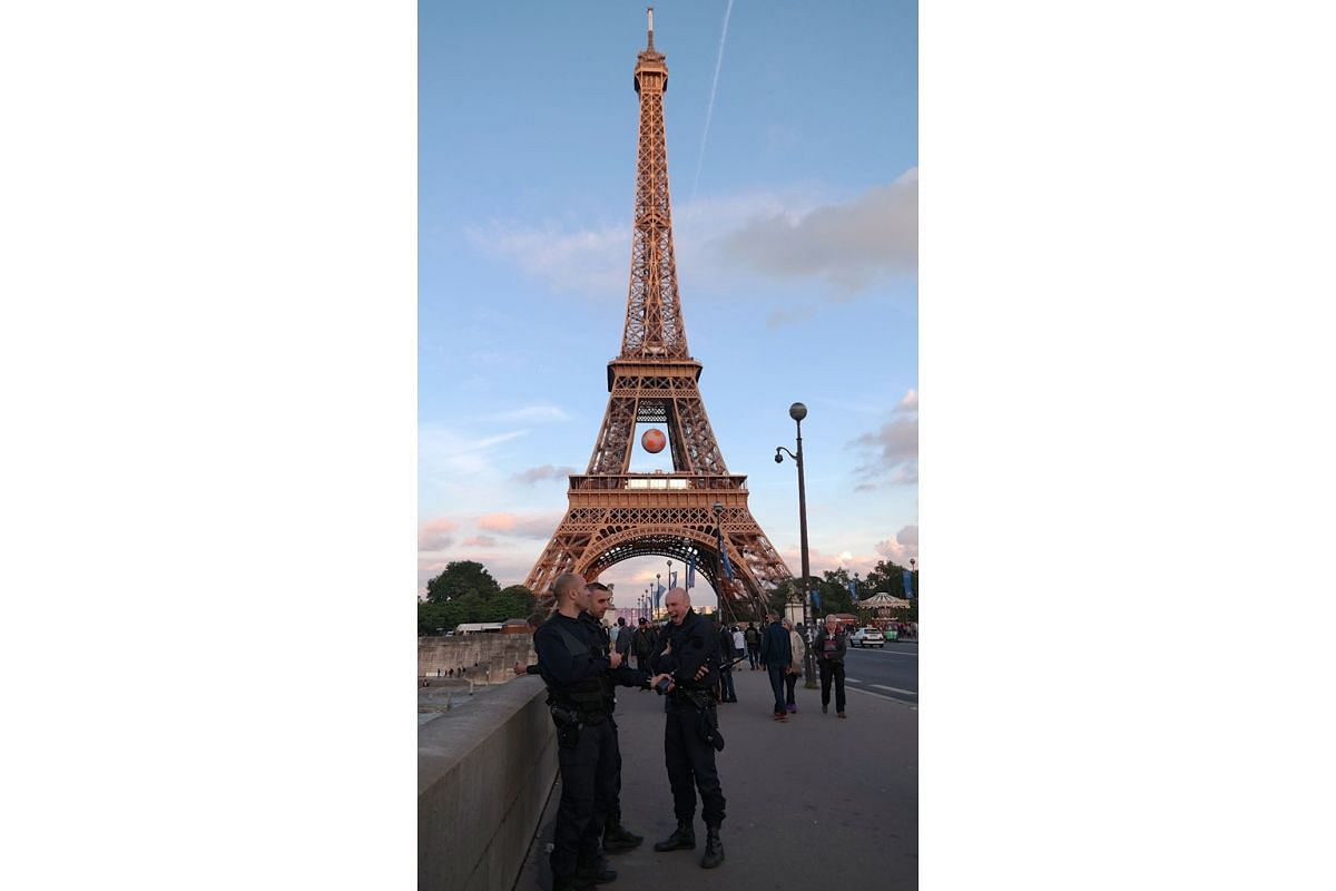 Armed policemen patrolling a bridge leading to the Eiffel Tower. Police and military presence is at a high in the French capital thanks to a series of terror attacks since last year and large crowds descending on the city this month for the Euro 2016