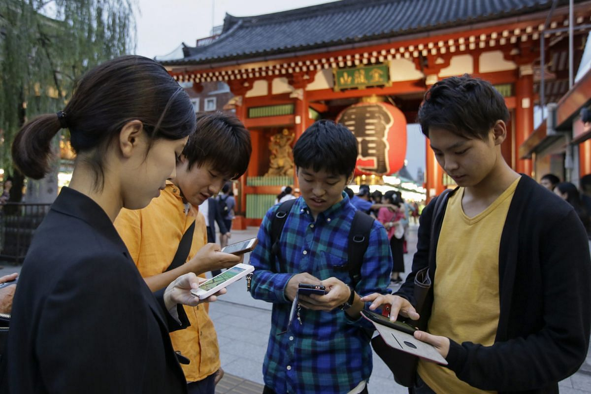 Japanese students playing Nintendo's hit mobile game Pokemon Go in Tokyo last week. The game, which uses GPS to locate the smartphone's location, has gained a huge following among smartphone users.