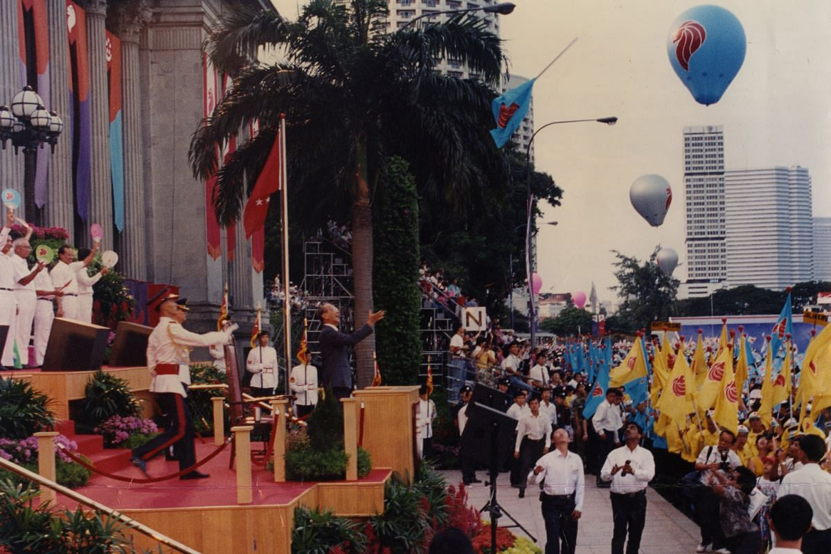 An over-exuberant participant throwing his flag into the air as President Wee Kim Wee reaches out to catch it during the National Day Parade at the Padang in 1993.