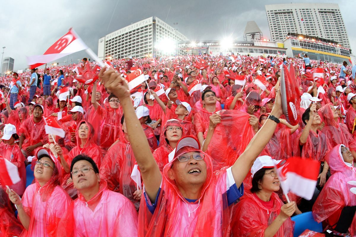 1: Mr Edwin Oh (centre), 61, enjoying the performance by the Red Lions in spite of the rain at the 2008 parade at Marina Bay.