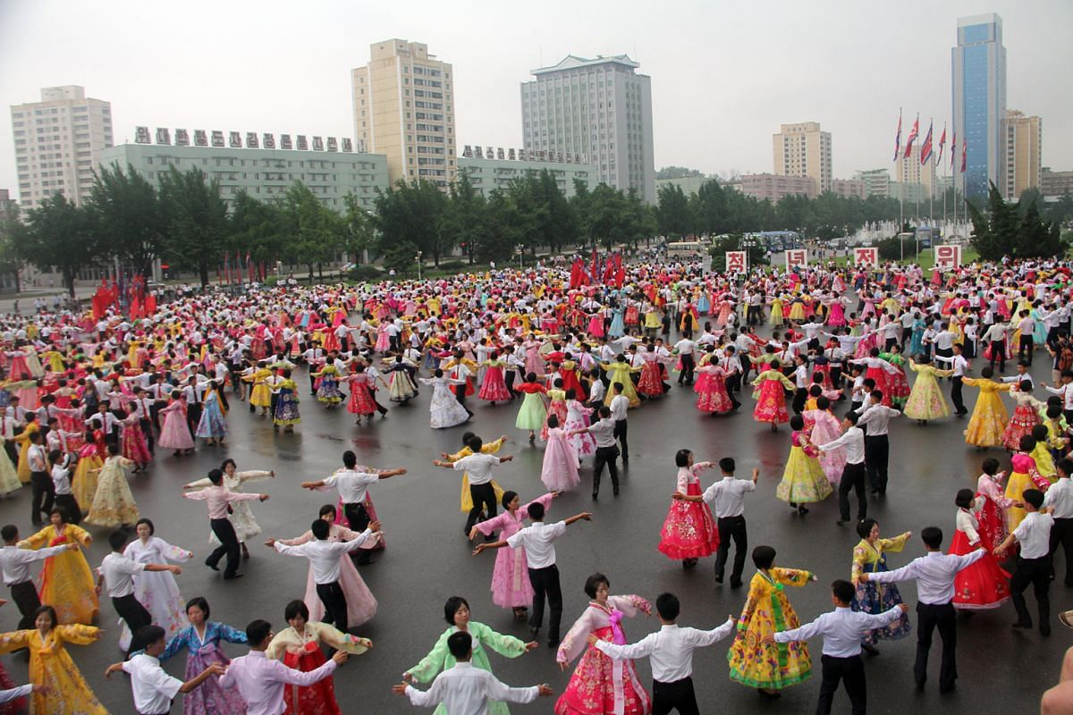 On Victory Day, university students perform mass dances at Kim Il Sung Square (above) while other North Koreans pay their respects at the towering bronze statues of late presidents Kim Il Sung and Kim Jong Il (left). Cycling is a popular way to get a