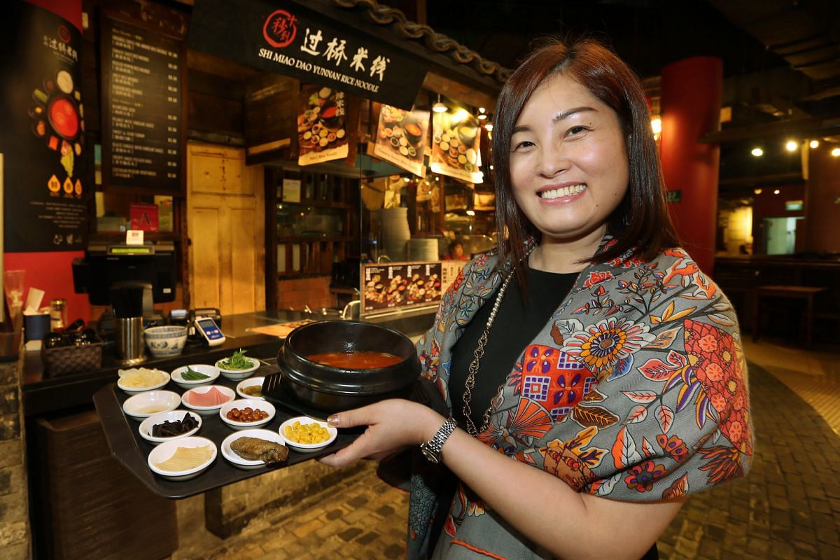 Ms Crystal Chou, owner of Shi Miao Dao Yunnan Rice Noodles in Singapore, with the Tomato noodle set, which comes with 11 side items.