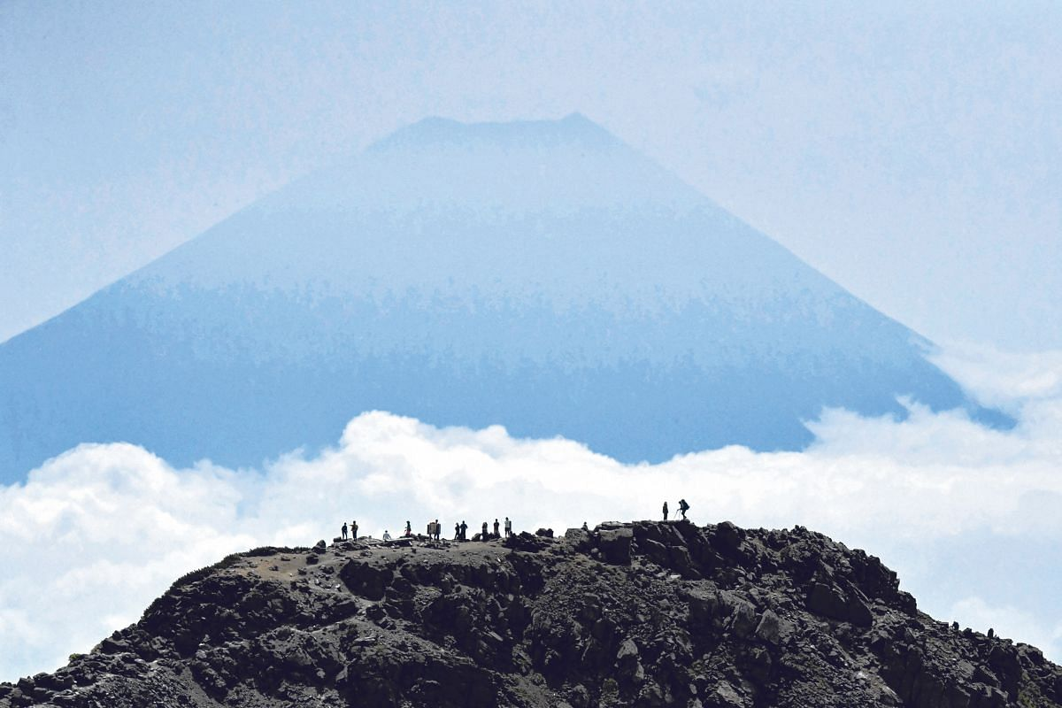 Trekkers enjoying the view of Mount Fuji from the summit of Mount Kitadake on the newly created Mountain Day national holiday on Aug 11.