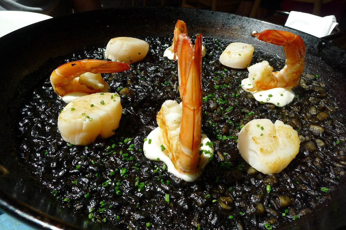 """Steamed Mussels With """"Bouillabaisse"""" (above) and Squid Ink Paella (left)."""