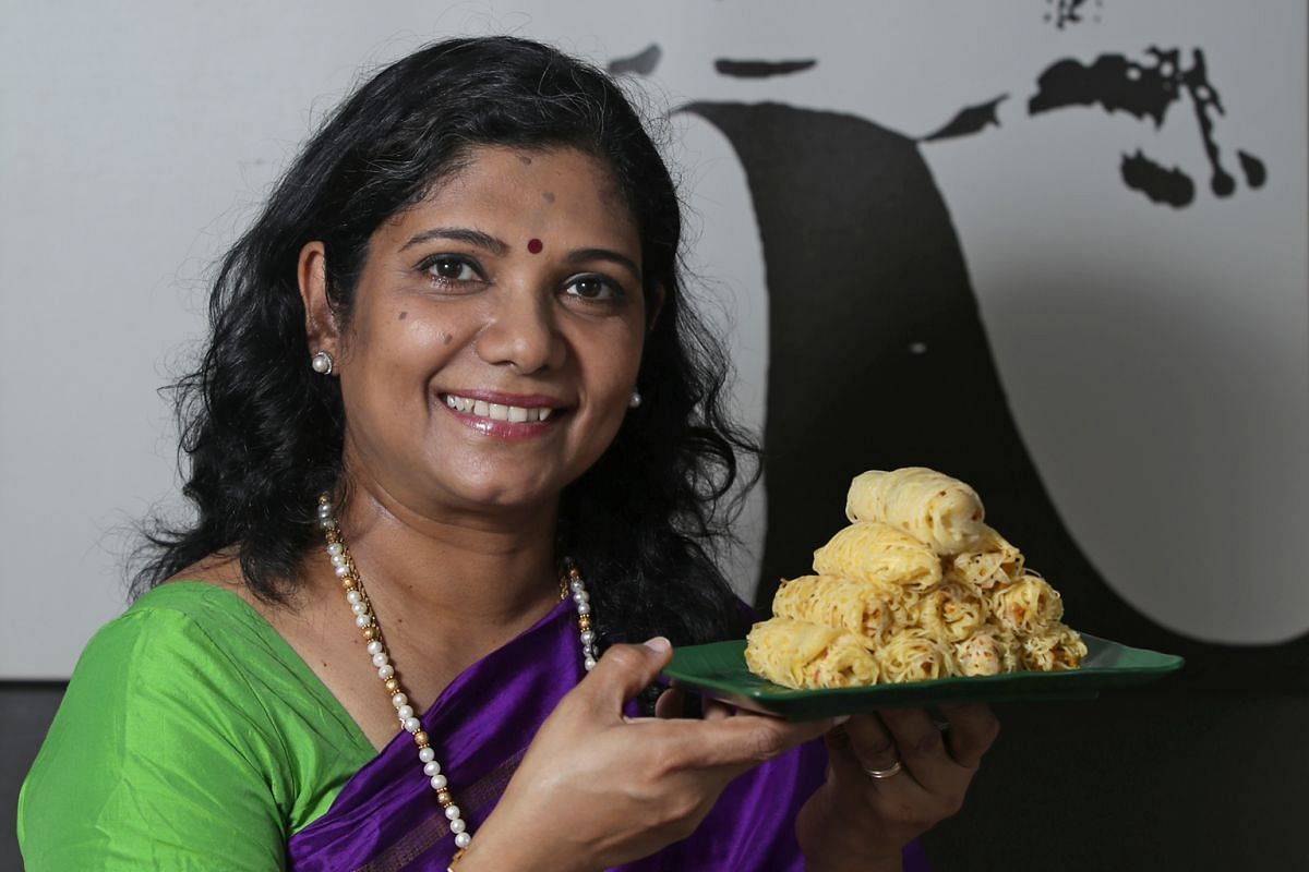 A traditional roti jala mould (far left) is made of metal, while the modern one is made of plastic and has bigger holes, which may lead to thicker crepes. Mrs Komala Selvan stuffs her roti jala with a dry chicken and potato curry.