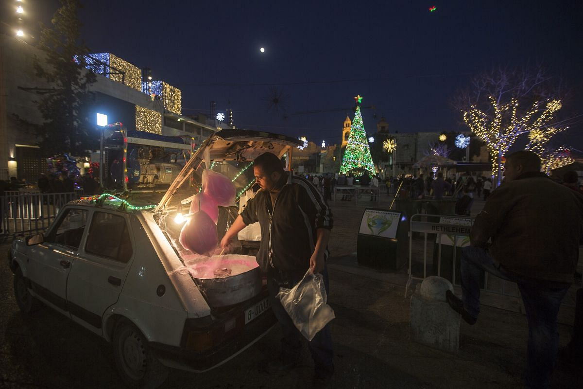 A Palestinian man sells cotton candy from the trunk of his car at the Manger square next to the Church of Nativity, accepted by Christian tradition as the birthplace of Jesus Christ, in the West Bank city of Bethlehem, on Dec 23, 2015.